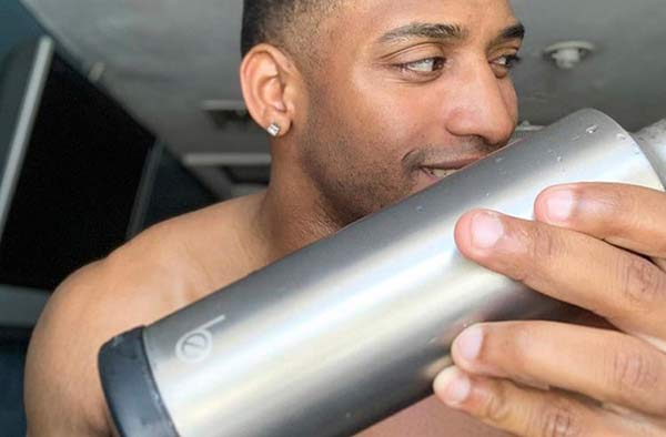 man holding stainless steel reusable water bottle