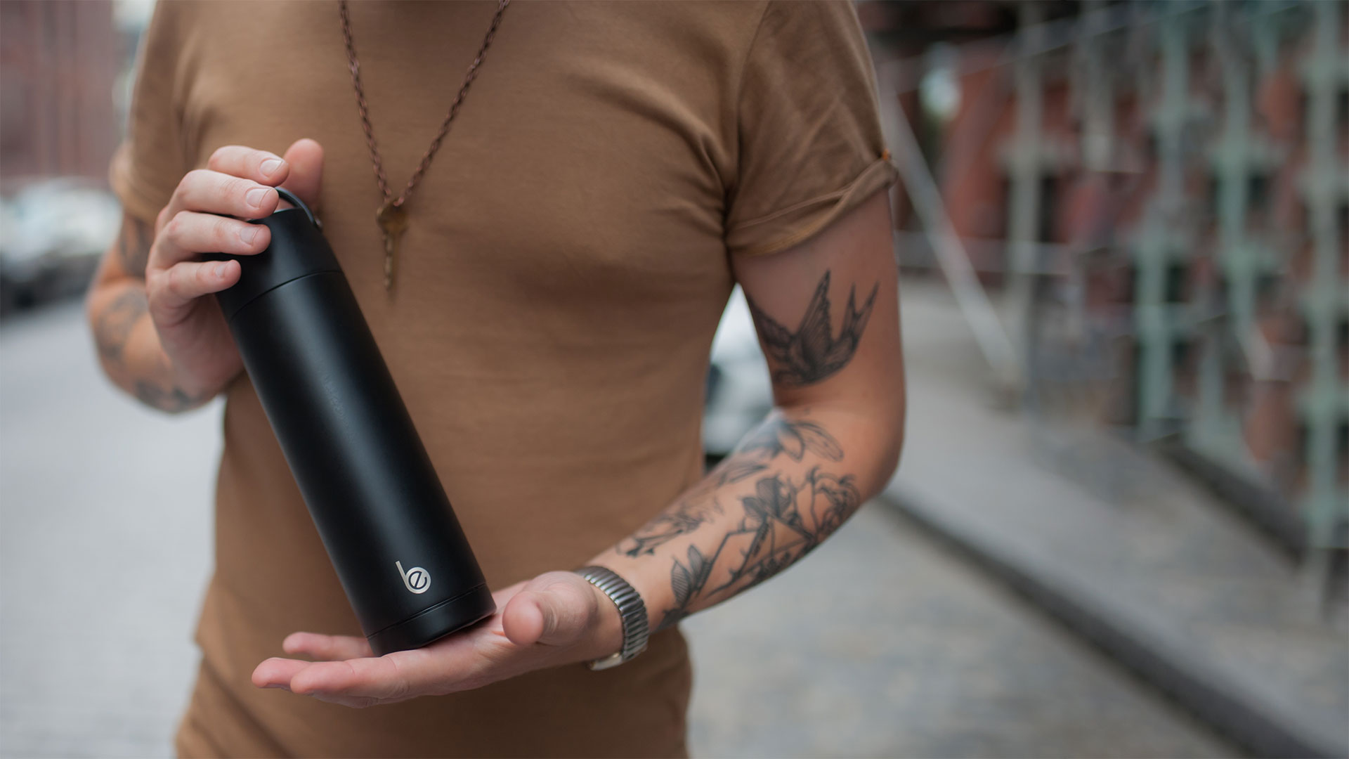 man holding a stainless steel reusable water bottle