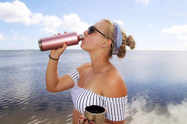 woman drinking from a stainless steel reusable water bottle